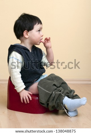 A cute toddler child boy sitting on a red potty. - stock photo