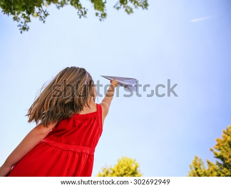 a cute toddler girl in a red dress throwing a paper airplane into the sky while a real plane is passing overhead in a park during summer time - stock photo
