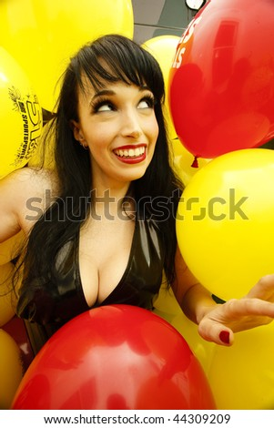 a cute woman surrounded by colorful balloons. - stock photo