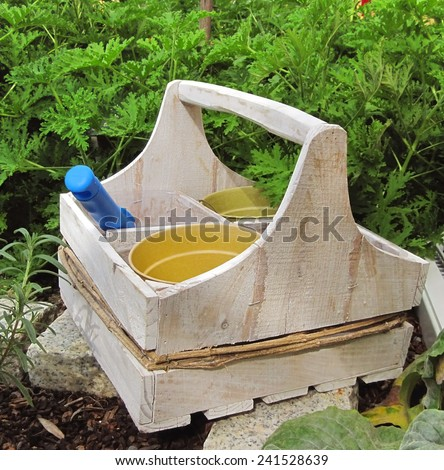 A cute wooden box holding gardening tools and flower pots sits in a lush, green garden                              - stock photo