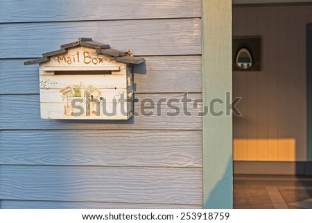 A cute wooden vintage mailbox hanging on a wooden wall - stock photo