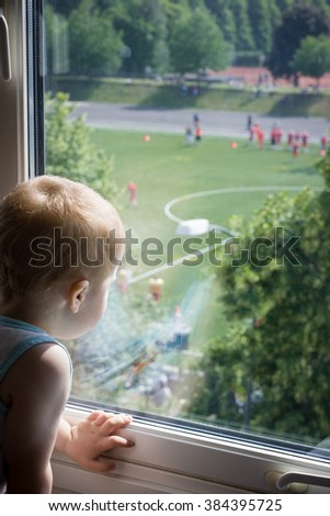 A cute 2 years old baby boy watching a soccer or a football game from his window. Sport fan. - stock photo