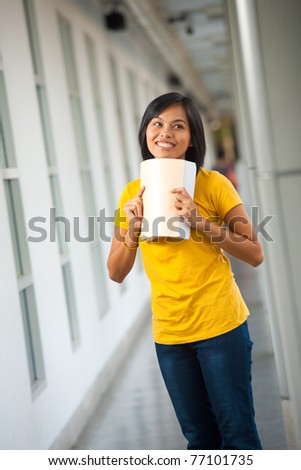 A cute young Asian student smiles while bending her textbook in a university campus hallway.   20s female Asian Thai model of Chinese descent. - stock photo