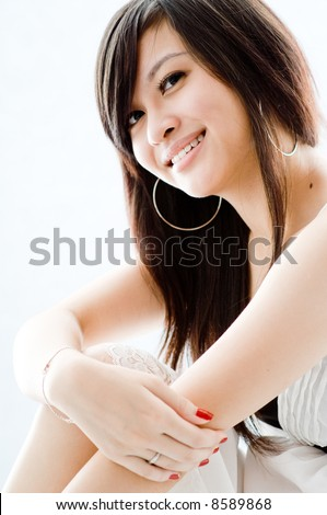 A cute young Asian teenager in white dress on white background - stock photo