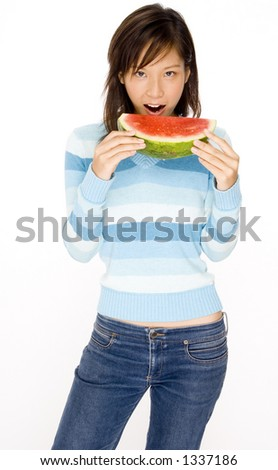 A cute young asian woman eating a slice of watermelon