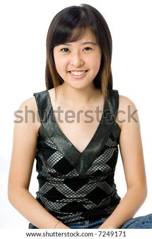 A cute young Asian woman in black and silver top and jeans on white background