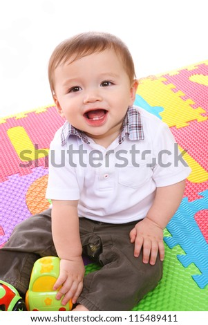 A cute young baby boy playing with his colorful toys - stock photo