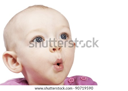 A cute young baby girl looking up with large eyes and pouting with her lips - stock photo