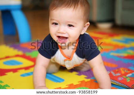 A cute young boy baby playing inside home with colorful toys - stock photo
