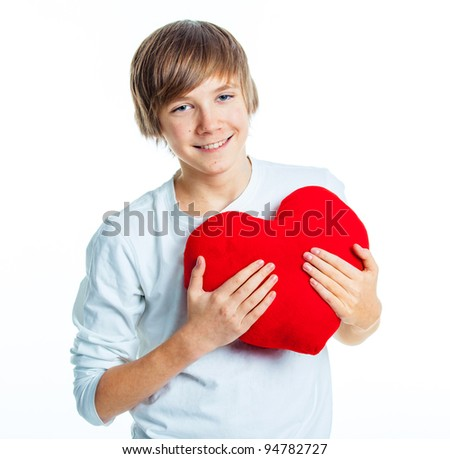 A cute young boy in love with a red plush heart in his hands. Focus on the heart. - stock photo