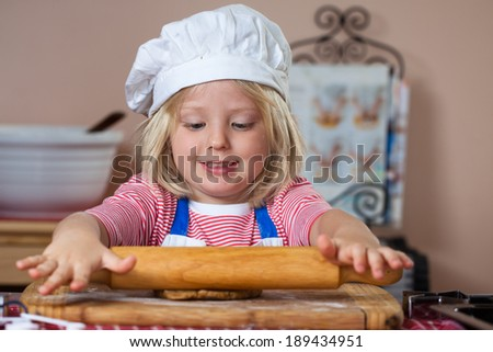 A cute young boy is baking and rolling out a ginger bread dough - stock photo