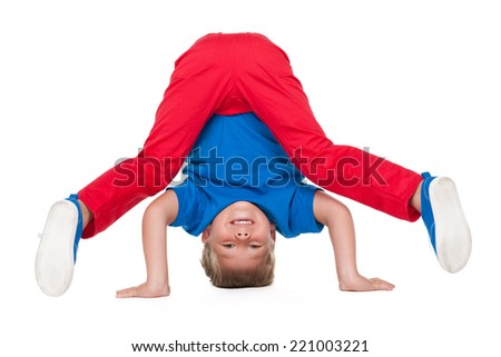 A cute young boy is dancing on the white background - stock photo