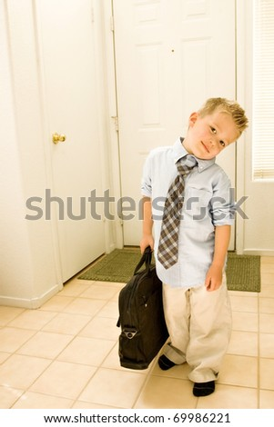 A cute young boy is dressed as a businessman, and stands by the door, carrying a briefcase - stock photo