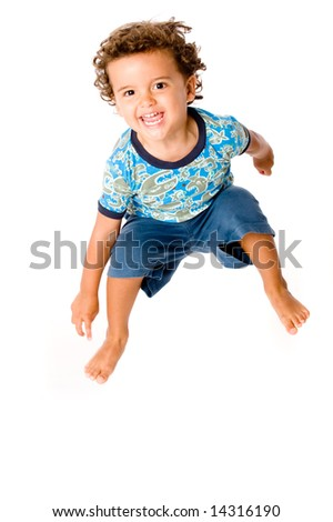 A cute young boy jumping in the air on white background - stock photo