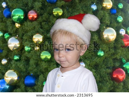 a cute young boy stands in front of christmas tree wearing Santa hat - stock photo