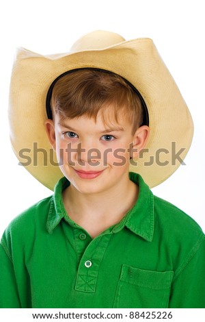 A cute young boy wearing a cowboy hat. - stock photo