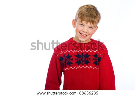 A cute young boy wearing a red Christmas sweater. - stock photo