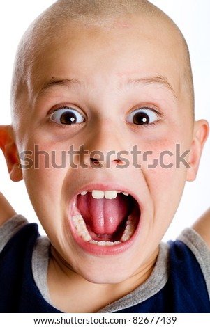 A cute young boy with a crazy expression on his face. - stock photo