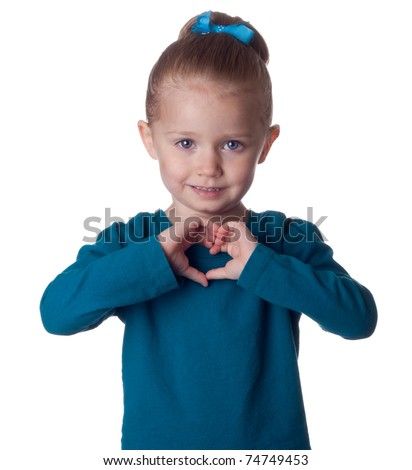 A cute young child forms the shape of a heart in her hands. - stock photo