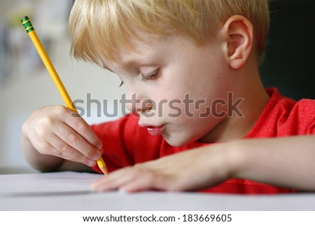 a cute young child is making a funny face as he is working at drawing on paper with a pencil - stock photo