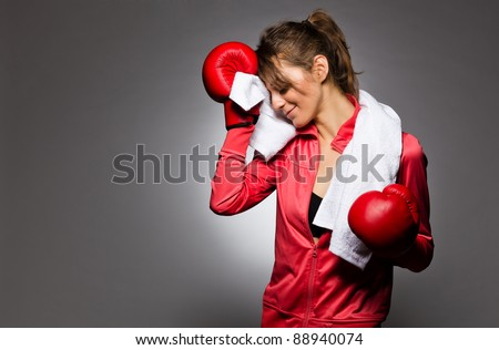 A cute young female wiping her sweat after a boxing session - stock photo