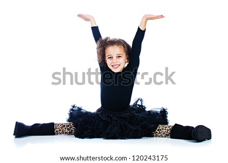A cute young girl doing the splits with her arms raised. - stock photo