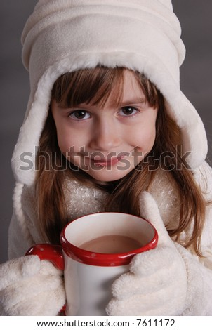 A cute young girl drinking hot chocolate - stock photo