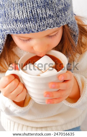 A cute young girl drinking hot chocolate with marshmallow - stock photo
