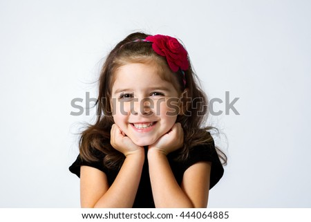 A cute, young girl grins with her chin in her hands. - stock photo