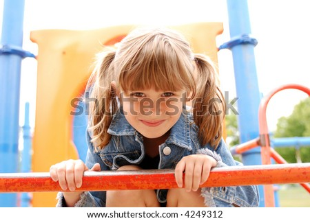 A cute young girl having fun on the jungle gym - stock photo