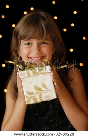 A cute young girl holding  a christmas gift, dark background with christmas light bokeh - stock photo