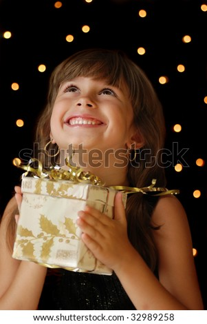 A cute young girl holding a christmas gift,dark background with christmas light bokeh - stock photo
