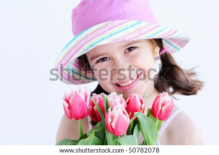 A cute young girl holding a pot of tulips - stock photo