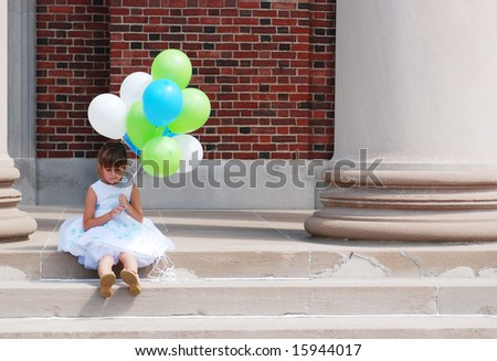 A cute young girl holding balloons - stock photo