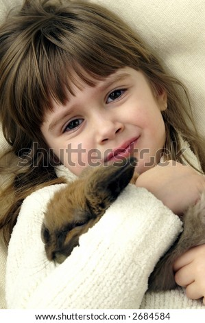 A cute young girl holding her bunny rabbit - stock photo