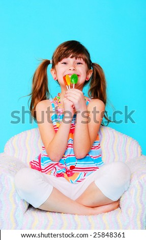 A cute young girl holding some suckers - stock photo