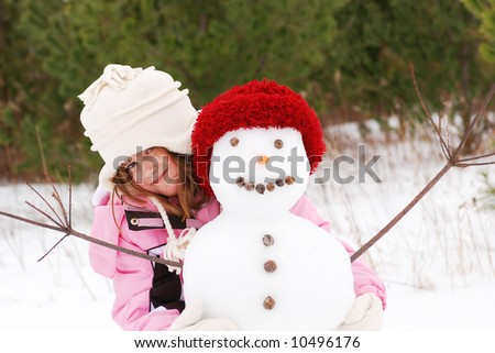 A cute young girl posing with her snowman - stock photo