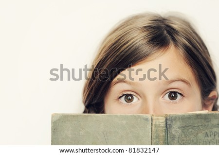 A cute young girl reading a book - stock photo