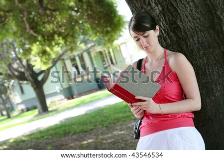 A cute young girl reading a book under tree outside home - stock photo