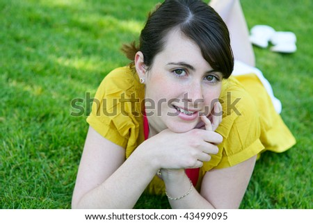 A cute young girl relaxing in the grass in park - stock photo