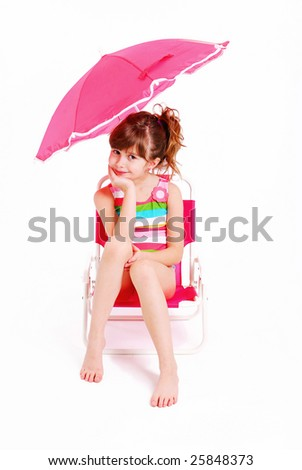A cute young girl sitting in a beach chair - stock photo