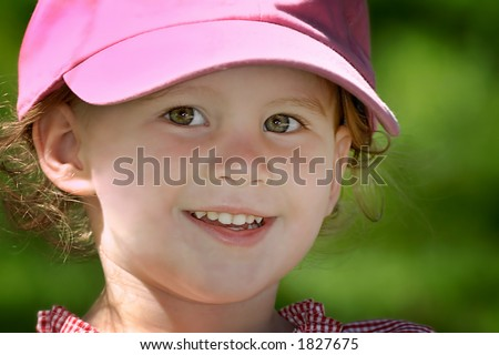 A cute young girl stops playing long enough to have her picture taken in her new baseball cap.