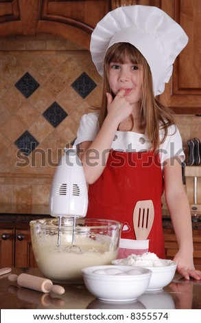A cute young girl tasting the cake batter - stock photo