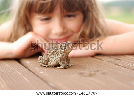 A cute young girl watching a toad - stock photo