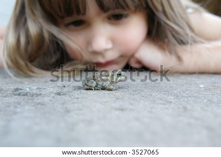A cute young girl watching a toad on the ground, shallow depth of field with focus on toad - stock photo