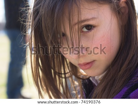 A cute young girl with an worried expression and a figure lurking behind her - stock photo