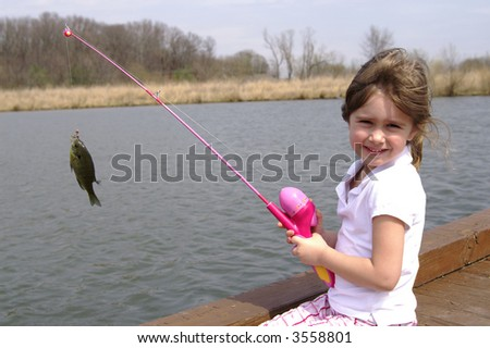 A cute young girl with her fishing pole and the blue-gill she caught - stock photo