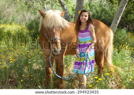 A cute young girl with her Icelandic Pony on a beautiful summer day