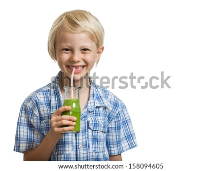 A cute young healthy boy drinking a green smoothie or juice through a straw. Isolated on white. - stock photo
