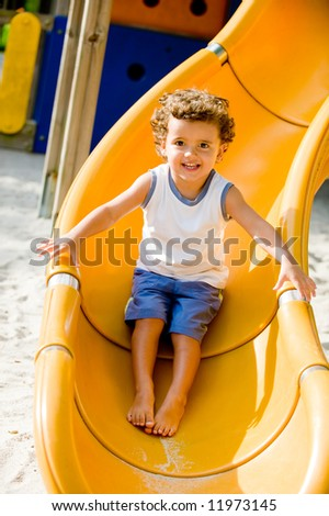 A cute young kid playing on a slide in a park